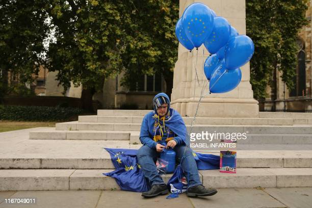 An antiBrexit protester inflates helium balloons with the EU flag outside the Houses of Parliament in London on September 9 2019 British Prime...