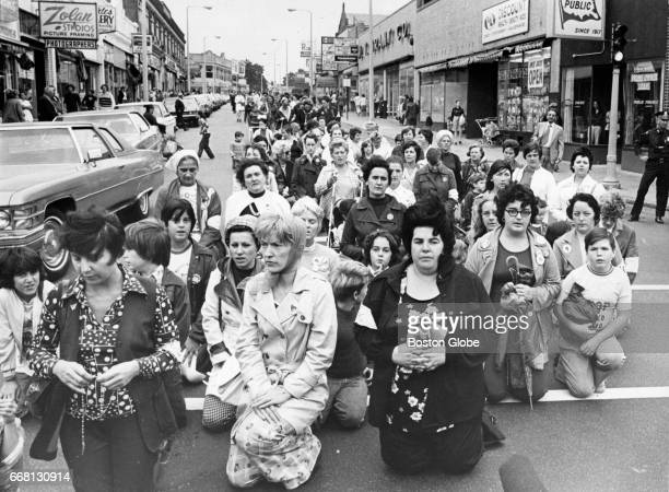 An antibusing Mothers March stops for a prayer at the junction of River Street and Hyde Park Avenue in Boston on Sep 12 1975 New bus route...
