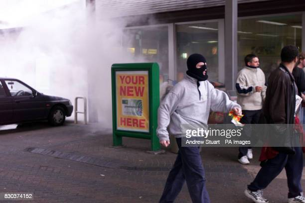 An anticapitalist demonstrator walks through the forecourt of the BP Garage in Kennington Lane south east London where dust rises from bags of cement...