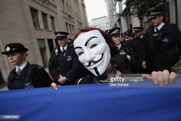An anticapitalist protester from the 'Occupy' movement holds a banner in front of police officers during a demonstration on May 1 2012 in London...