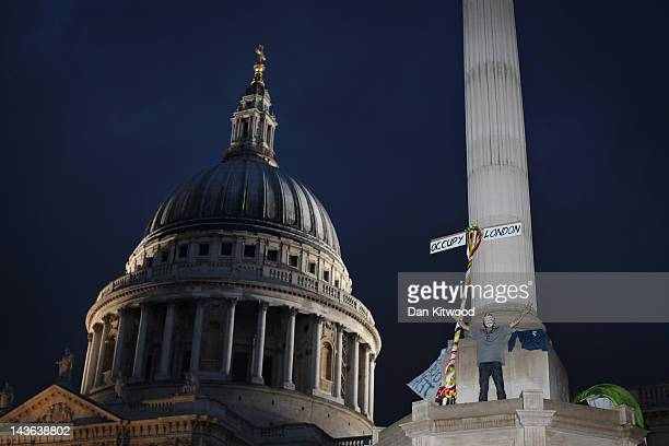 An Anticapitalist protester from the 'Occupy' movement scales a column in Paternoster Square which is adjacent to St Paul's Cathedral their previous...