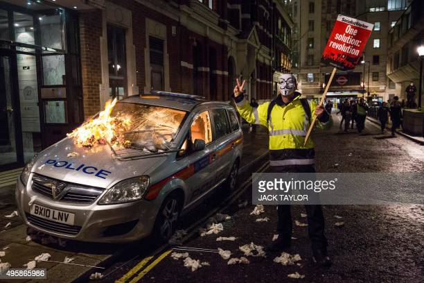An anticapitalist protester wearing a Guy Fawkes mask holds a placard as he stands alongside a burning police car during the 'Million Masks March'...