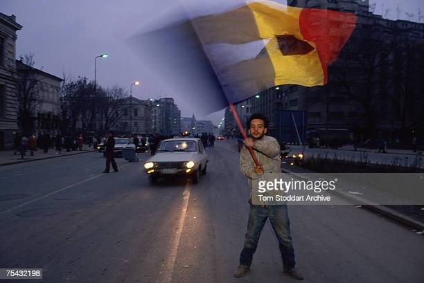 An antiCeausescu protestor waves a torn Romanian flag during the Romanian Revolution December 1989 The Communist coat of arms has been removed from...