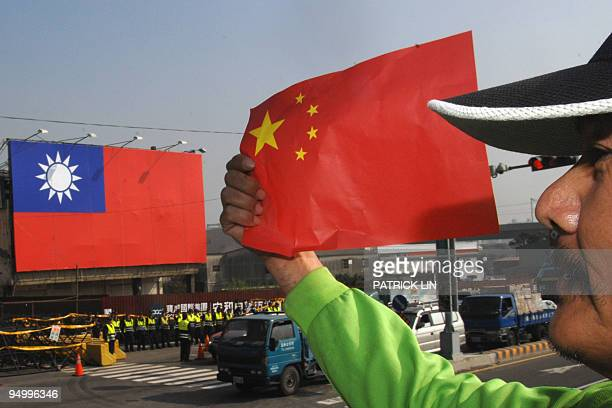 An antiChina protester holds the national flag of China during a demonstration outside of the Windsor hotel where a fresh round of talks between...