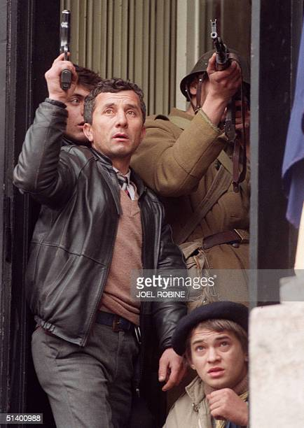 An antiCommunist civilian fighter along with a Romanian soldier supporting antiCeausescu's activists sheltered under a door to protect themselves...