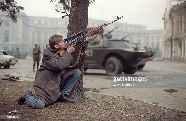 An antiCommunist Romanian civilian fights on December 24 1989 in downtown Bucharest as he returns fire against the supposedly Securitate secret...
