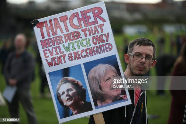 An antiConservative protester with a placrad featuring British former prime minister Margaret Thatcher and current British Prime Minister Theresa May...