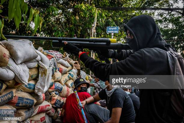 An anti-coup protester aims an improvised weapon on March 28, 2021 in Yangon, Myanmar. Myanmar's military Junta continued a brutal crackdown on a...