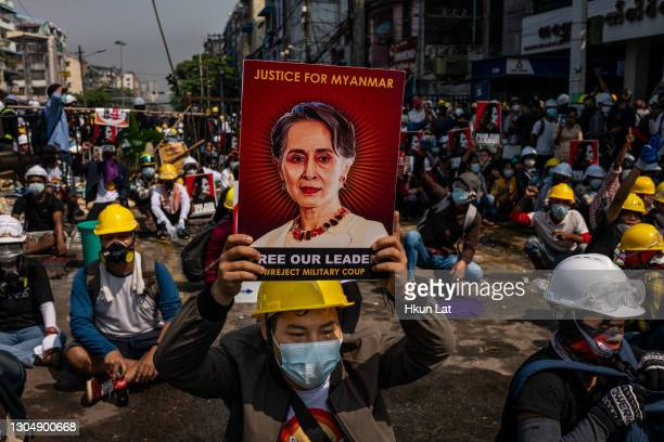 An anti-coup protester holds up a placard featuring de-facto leader Aung San Suu Kyi on March 02, 2021 in Yangon, Myanmar. Myanmar's military...