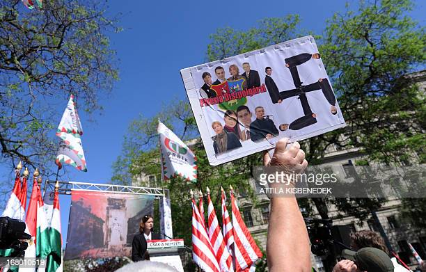 An antidemonstrator lifts a homemade picture with a Swastika and photos of the party leaders and representatives of the nationalist party of the...