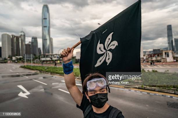 An antiextradition protester waves a black flag on a street outside the Legislative Council Complex ahead of the annual flag raising ceremony of 22nd...