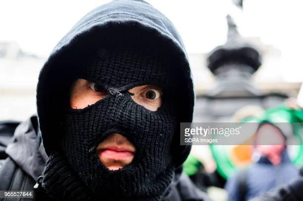 An antifa activist in black bloc wear approaches the camera in Piccadilly Circus as marchers against racism pass by in freezing conditions to mark...