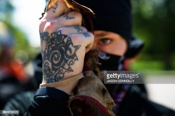 An Antifa demonstrator holds up the remains of a tattered and burned US national flag during the Denver March Against Sharia Law in Denver Colorado...