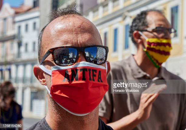 An Antifa protester wears his protective mask during a rally to demonstrate against Fascism, Nazism and racism on July 25, 2020 in Lisbon, Portugal....