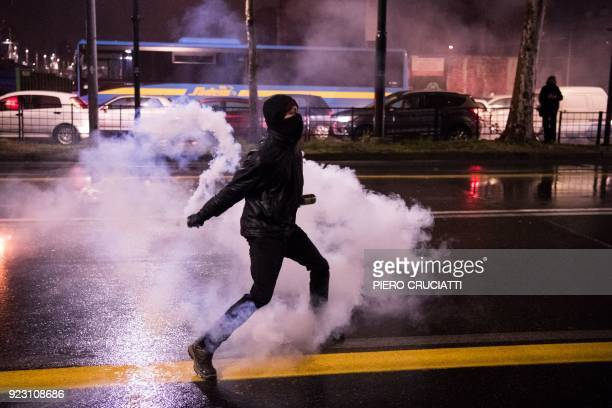 An Antifascist activist throws a tear gas canister at police officers during a rally against an election campaign meeting organized by far-right...