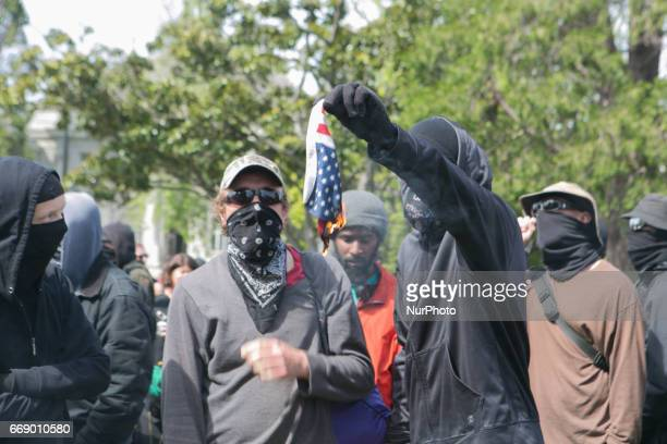 An antifascist lights an American flag on fire during a free speech rally at Martin Luther King Jr Civic Center Park in Berkeley California United...