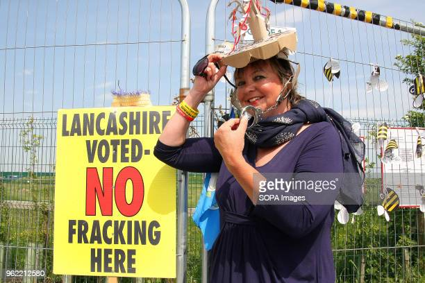 An AntiFrack Protester with a Tree Sculpture Hat adorned with Handcuffs poses at the security fence of Fracking company Cuadrilla's Frack site during...