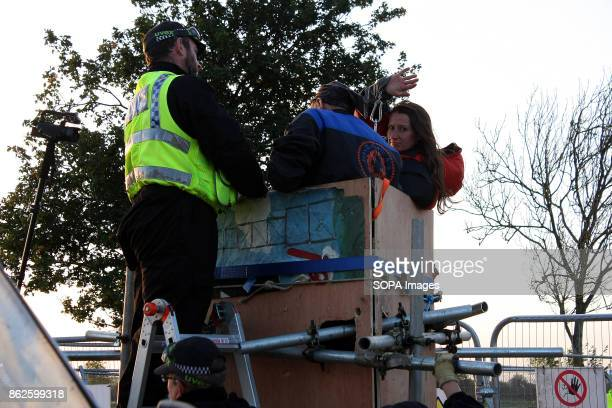 An AntiFracking protestor who has locked herself onto a wooden tower at a major Fracking site in attempt to block the entrance waves her chains to...
