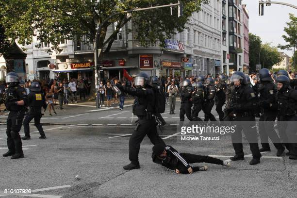 An antiG20 Summit protester lies on the ground as riot policemen charge during clashes on July 7 2017 in Hamburg Germany Authorities are braced for...