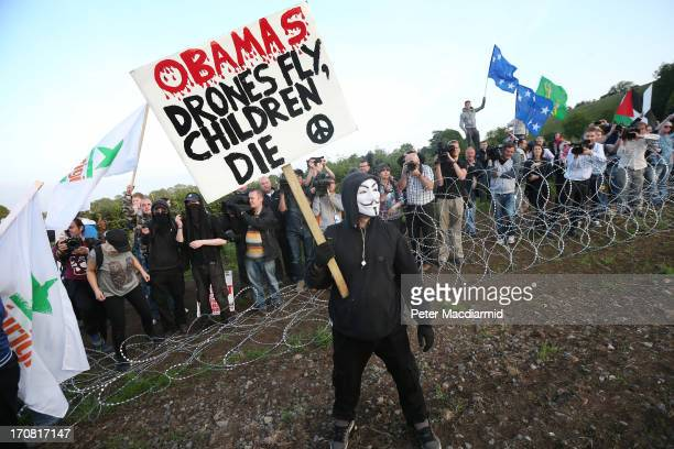 An antiG8 protester stands with a placard after breaking through the outer perimeter razor wire fence around the G8 summit venue at Lough Erne on...