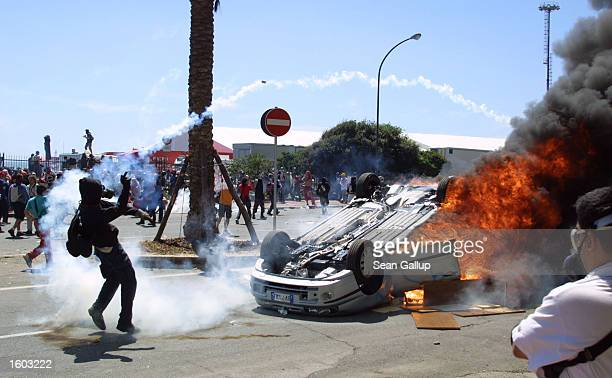 An antiG8 protester throws a tear gas canister back at police while a car burns nearby during street fighting July 21 2001 in Genoa Italy Several...
