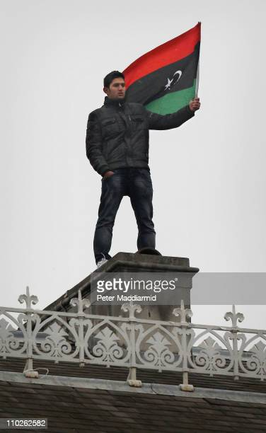 An anti-Gaddafi protestor waves a flag from the roof of the Libyan Embassy on March 17, 2011 in London, England. Police are surrounding the embassy...
