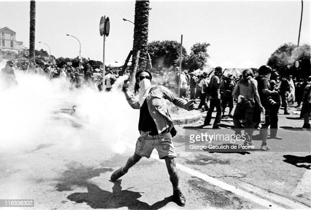 An antiglobalisation activist throws back a tear gas grenade at police during a protest against the 27th G8 Summit In Genoa on July 21 2001 in Genoa...