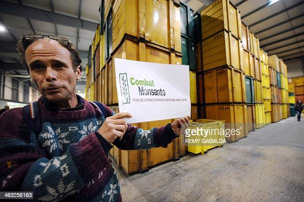 An antiGMO activist holds a placard reading 'Fight Monsanto so that Monsanto's world doesn't become ours' after antiGMO activists entered a...