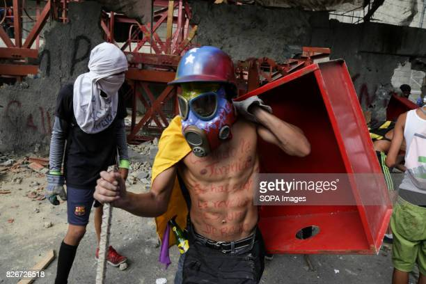 An antigovernement activist wearing a gas mask to protect himself against the smoke is seen holding a metal box while protesting against the newly...