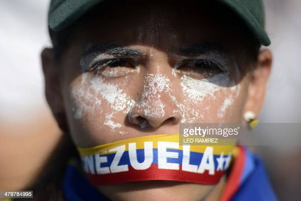An antigovernment activist demonstrates against Venezuelan President Nicolas Maduro in Caracas on March 20 2014 Demonstrators clashed with riot...