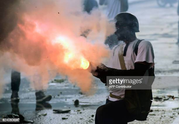 An antigovernment activist fires a improvised weapon during clashes with riot police in a protest in Caracas on July 28 2017 Protesters took over...