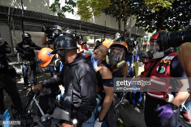 An antigovernment activist is assisted and carried away on a motorbike during clashes with the police during a 48hour general strike called by the...