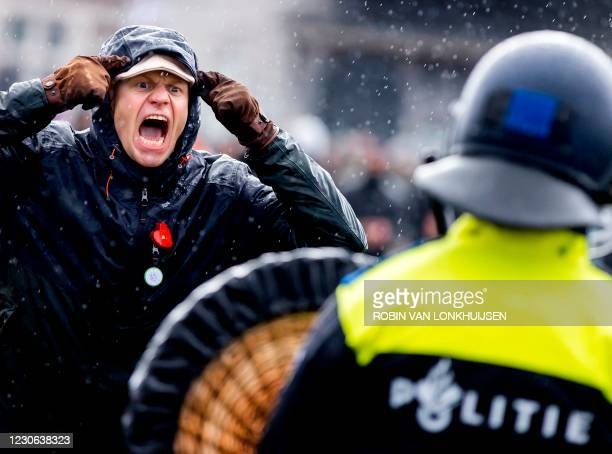 An anti-government activist screams at a Dutch police officer during a protest to denounce ongoing restrictions related to the coronavirus disease...