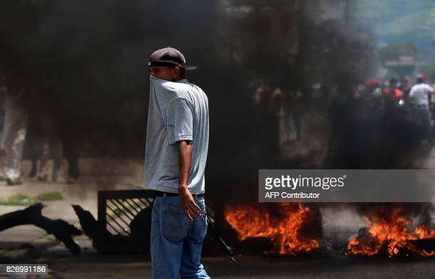 An antigovernment activist stands near a barricade burning in flames in Venezuela's third city Valencia on August 6 a day after a new assembly with...