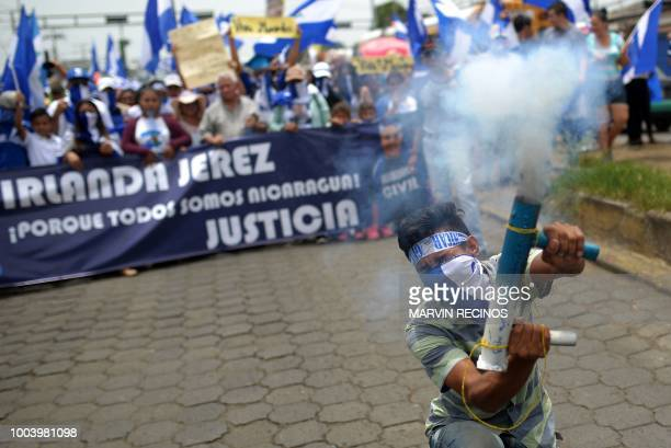 An antigovernment demonstrator fires a homemade mortar as he takes part in a march in Managua on July 22 2018 demanding the resignation of Nicaraguan...