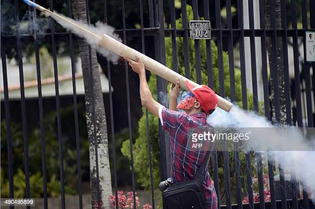 An anti-government demonstrator fires a homemade rocket during confrontations with riot police during a protest against the government of President...