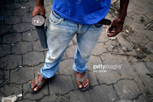 An antigovernment demonstrator holds a handmade mortar in Masaya Nicaragua on June 8 2018 Demand for the makeshift shells has jumped in recent weeks...