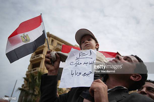 An antigovernment demonstrator holds his child aloft in Tahrir Square in sight of The Egyptian Museum on February 4 2011 in Cairo Egypt...