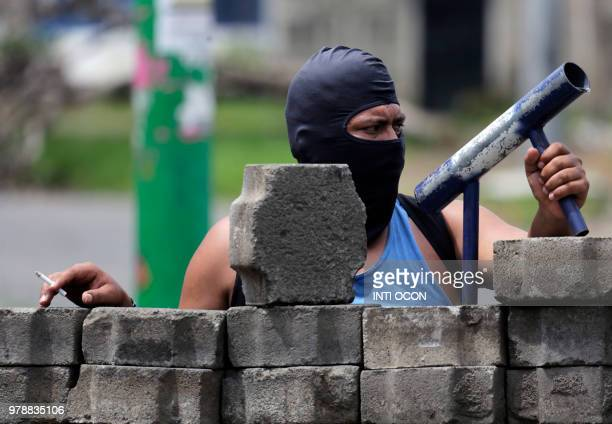 An antigovernment demonstrator holds his handmade mortar as he takes cover behind a barricade during clashes with riot police and members of the...