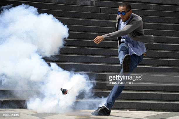 An antigovernment demonstrator kicks a tear gas canister during confrontations with riot police during a protest against the government of President...