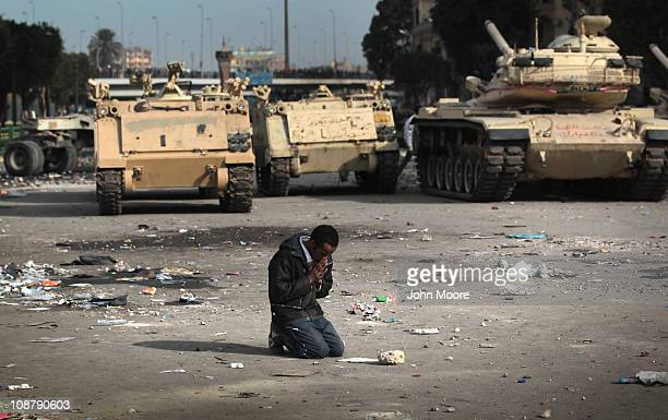 An antigovernment demonstrator prays near Egyptian army vehicles on February 3 2011 in Cairo Egypt The Army positioned tanks between the protesters...