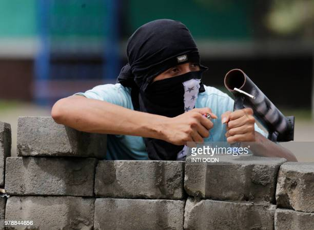 An antigovernment demonstrator prepares to fire his handmade mortar as he takes cover behind a barricade during clashes with riot police and members...