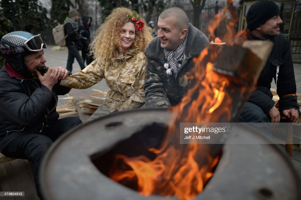 An anti-government demonstrator sits by a brazier outside the Ukrainian parliament on February 25, 2014 in Kiev, Ukraine. Ukraine's interim President Olexander Turchynov is due to form a unity government, as UK and US foreign ministers meet to discuss emergency financial assistance for the country.