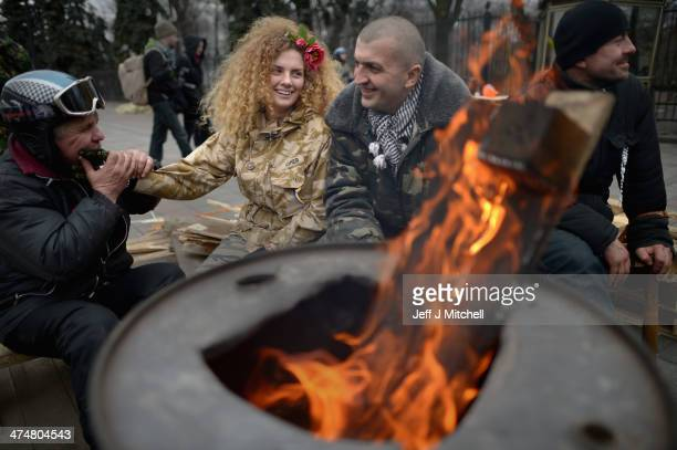 An antigovernment demonstrator sits by a brazier outside the Ukrainian parliament on February 25 2014 in Kiev Ukraine Ukraine's interim President...
