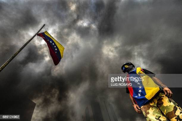 TOPSHOT An antigovernment demonstrator stands next to a national flag during an opposition protest blocking the Francisco Fajardo highway in Caracas...