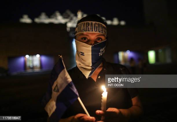 TOPSHOT An antigovernment demonstrator takes part in a vigil to demand the release of political prisoners and justice for the victims of protests...