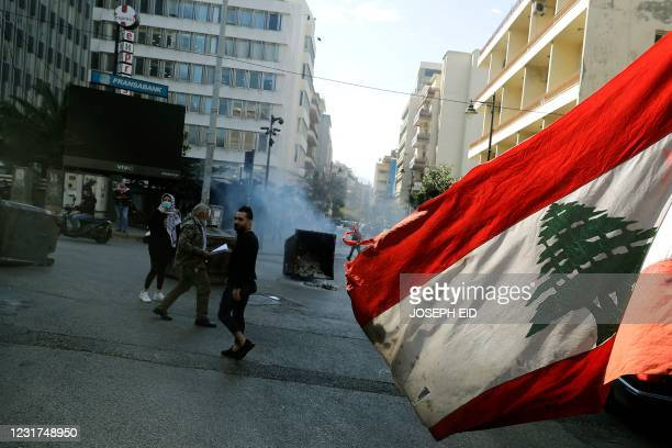 An anti-government demonstrator waves the national flag as they block the street, with burning garbage dumpsters, in front of Lebanon's central bank...