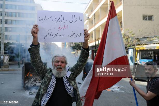 """An anti-government demonstrators carries a placard which reads """"The bank is safe, the currency is dead"""" block the street, with burning garbage..."""