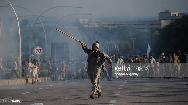 An anti-government protester, armed with baton, runs during clashes with Pakistani policemen in Islamabad, Pakistan on September 1, 2014. Clashes...