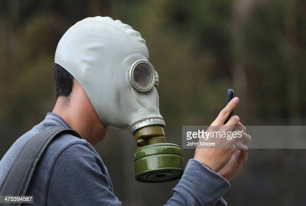 An antigovernment protester checks his smart phone during a demonstration on February 27 2014 in Caracas Venezuela Almost three weeks after protests...